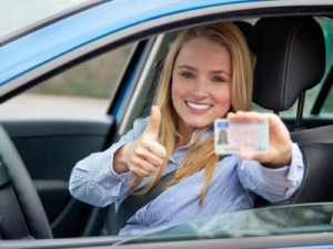 Das Mädchen hält den Autoführerschein stolz in der Hand