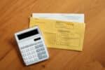 Sitzen Sie mit dem Handy zwischen Ohr und Schulter am Steuer, müssen Sie mit einem Bußgeld rechnen.