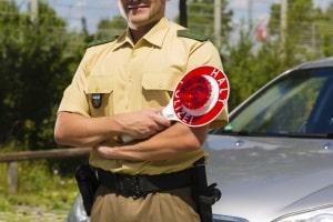 Der Polizist regelt den Verkehr mit Handzeichen, obwohl die Ampel intakt ist? Die Polizei hat Vorrang!
