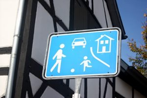 Sie fahren jetzt in eine Spielstraße ein. Dieses Verkehrsschild macht Ihnen das deutlich.