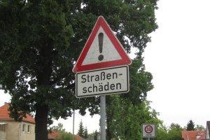 Wird auf Straßenschäden durch ein Schild hingewiesen, gilt es die Fahrweise anzupassen.